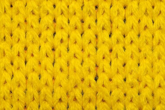 Gelbe synthetische strickware nahaufnahme. gewirke textur hintergrund
