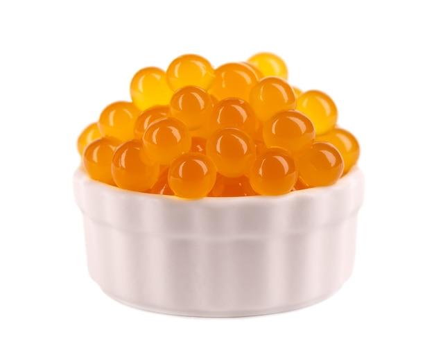 Gelbe tapiokaperlen für bubble tea auf weißem hintergrund. tapiokaperlen in weißer keramikschale.