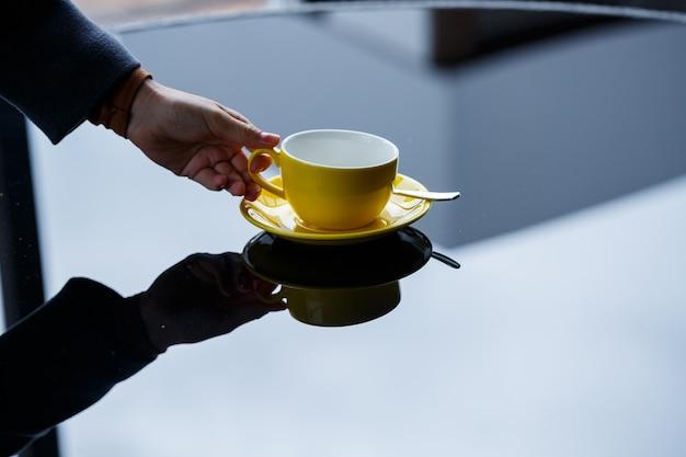 Gelbe tasse für kaffee oder tee mit einer untertasse in den händen eines mädchens auf dem hintergrund eines glastisches.