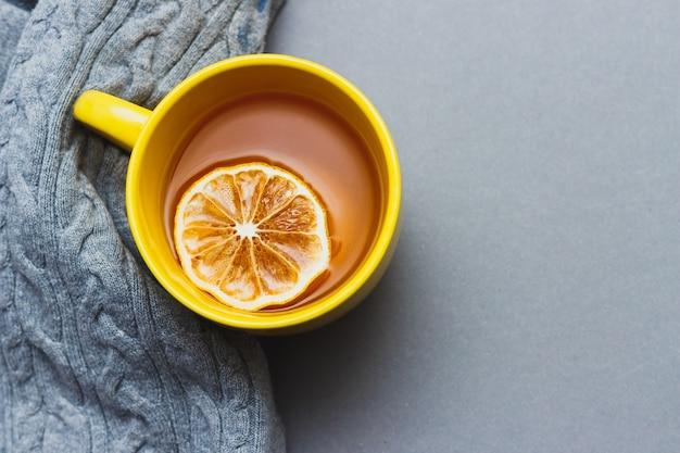 Gelbe tasse kaffee auf grauem hintergrund mit platz für text. helles stilllebenkonzept mit farben 2021. draufsicht.