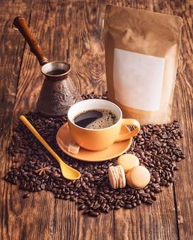 Gelbe tasse kaffee, makronen, bohnen, türkische kaffeekanne und bastelpapierbeutel auf hölzernem hintergrund
