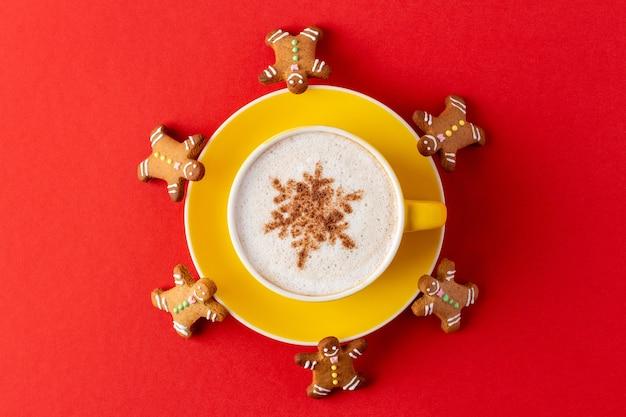 Gelbe tasse kaffee verziert mit schneeflocke, umgeben von lebkuchenmännern auf rot