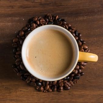 Gelbe tasse mit kaffeebohnen herum