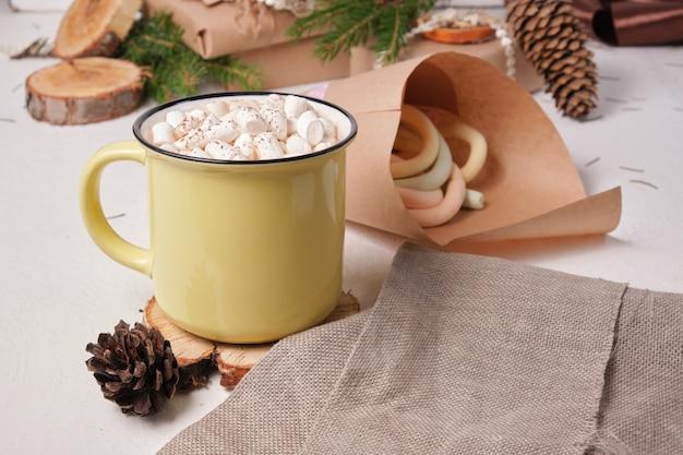 Gelbe tasse mit kakao dekoriert mit marshmallows auf einem ständer aus sägeschnittholz, eine tasche mit marshmallows, ein fichtenzweig und weihnachtsgeschenke im hintergrund