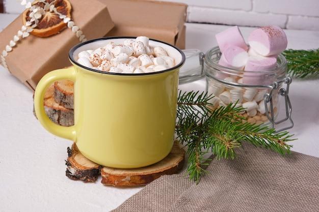 Gelbe tasse mit kakao verziert mit marshmallows auf einem ständer aus sägeschnittholz, einem glas marshmallows, einem fichtenzweig und weihnachtsgeschenken im hintergrund