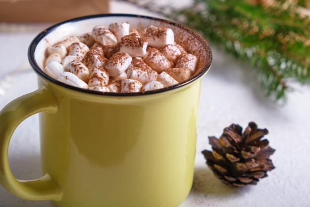 Gelbe tasse mit kakao verziert mit marshmallows nahaufnahme, tannenzweig und tannenzapfen im hintergrund