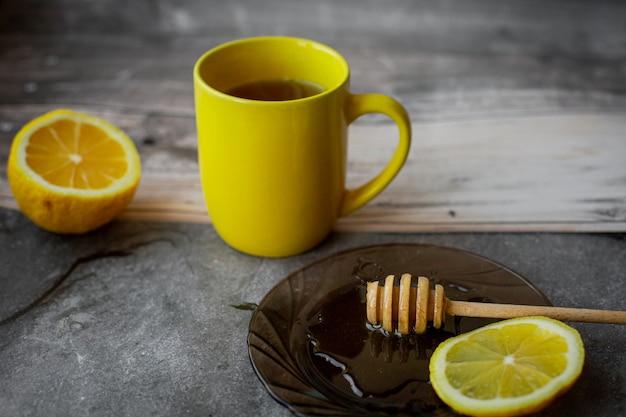 Gelbe tasse, tropfender honig auf einer untertasse auf grau