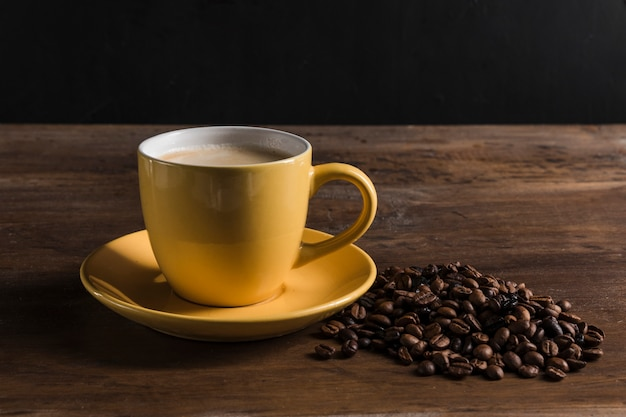 Gelbe tasse und kaffeebohnen