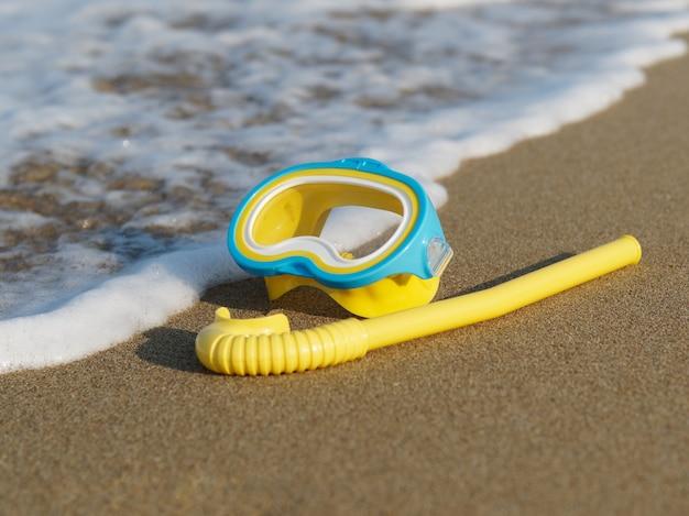 Gelbe tauchmaske und schnorchel für kinder auf dem strandsand mit weicher ozeanwelle.
