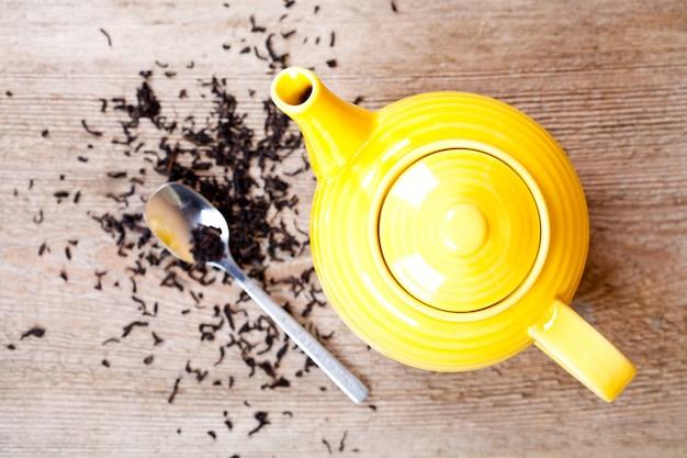 Gelbe teekanne mit löffel und tee