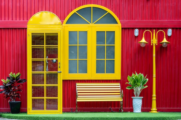 Gelbe telefonzelle, bank und laternenpfahl auf dem hintergrund einer roten metallwand auf der straße der stadt danang in vietnam