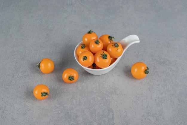 Gelbe tomaten auf steinoberfläche isoliert