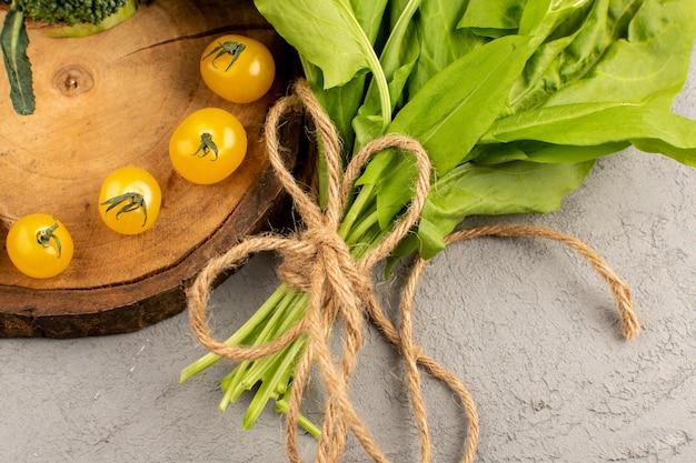 Gelbe tomaten der draufsicht zusammen mit grünem salat auf dem grauen boden