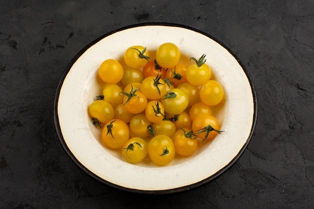 Gelbe tomaten frisch in weißer platte auf einem grau