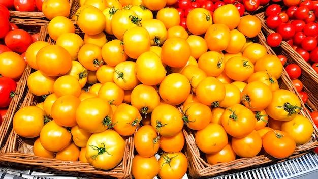 Gelbe tomaten in einer schachtel auf einem regal in einem supermarkt. gelbe und rote tomaten mit schwänzen in einer draufsicht des plastikbehälters