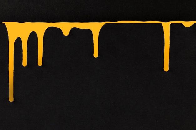 Gelbe tropfende farbe auf schwarzem hintergrund