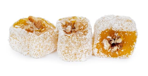 Gelbe türkische freude mit nüssen im puderzucker lokalisiert auf weißem hintergrund