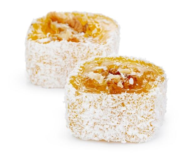 Gelbe türkische freude mit nüssen in puderzucker lokalisiert auf weiß