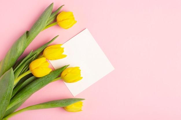 Gelbe tulpen auf einem rosa hintergrund, weiße postkarte zum schreiben