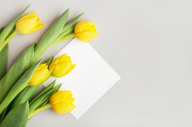 Gelbe tulpen auf grauem hintergrund, weiße postkarte zum schreiben