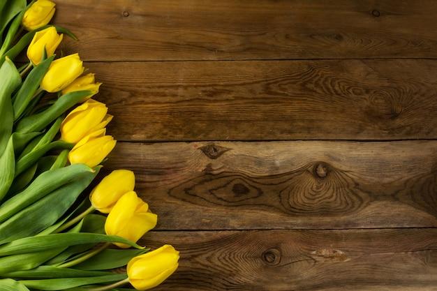 Gelbe tulpen auf hölzernem hintergrund, kopienraum