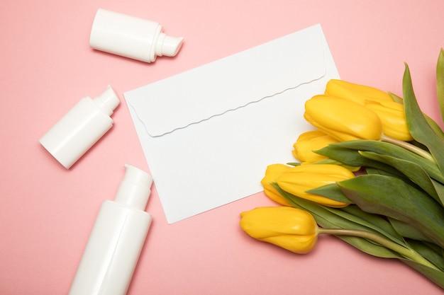 Gelbe tulpen auf rosa hintergrund mit kopierraumumschlag und kosmetikflaschenbehältern. attrappe, lehrmodell, simulation. glücklicher muttertag, frauentag glückwunschkonzept