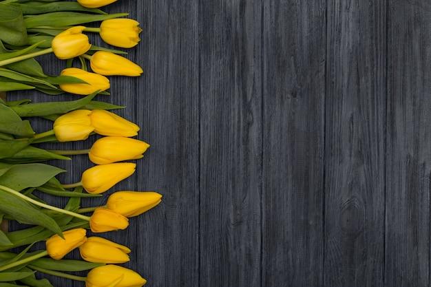 Gelbe tulpen auf vintag hölzernem hintergrund. frühlingshintergrund mit tulpen, kopienraum für text. flachgelegt, draufsicht.