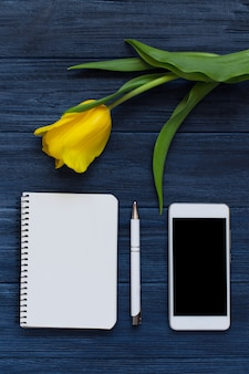 Gelbe tulpen des frühlinges, leeres notizbuch, stift und weißes intelligentes telefon. flachgelegt, draufsicht.