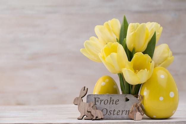 Gelbe tulpen, frühlingsblumen und osterdekoration.