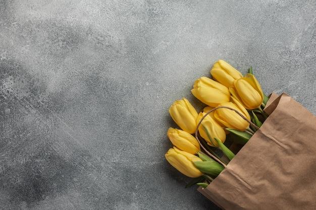 Gelbe tulpen in einer papiertüte auf einem grauen steinhintergrund. ansicht stürzen den platz für ihre inschrift.