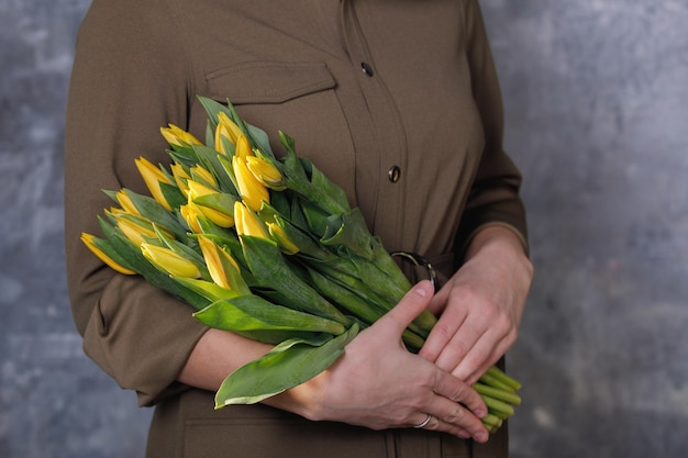 Gelbe tulpen in weiblichen händen auf einem neutralen grau