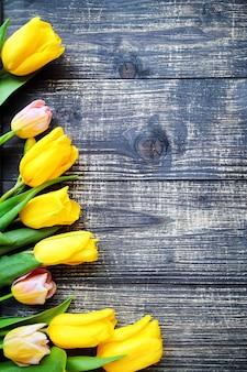 Gelbe tulpen liegen auf altem holztischhintergrund. frauentagskonzept. nahansicht. freier speicherplatz für ihren text.