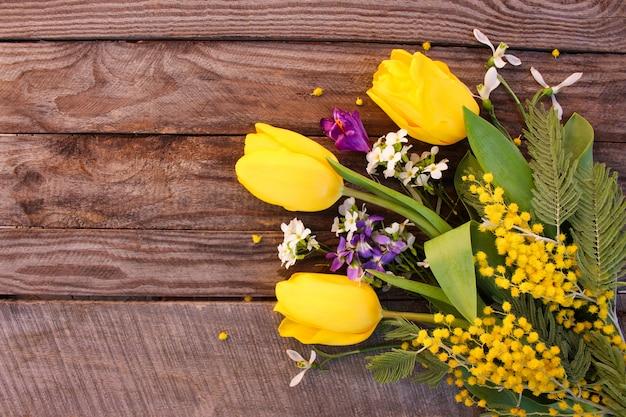 Gelbe tulpen, mimosen auf altem holz
