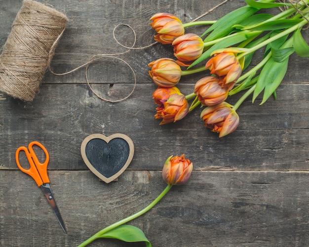 Gelbe tulpen mit rustikalem thread auf einem holztisch.