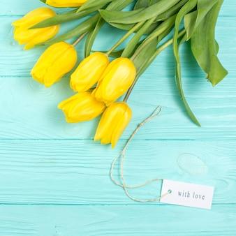 Gelbe tulpen und mit liebesaufschrift auf tabelle