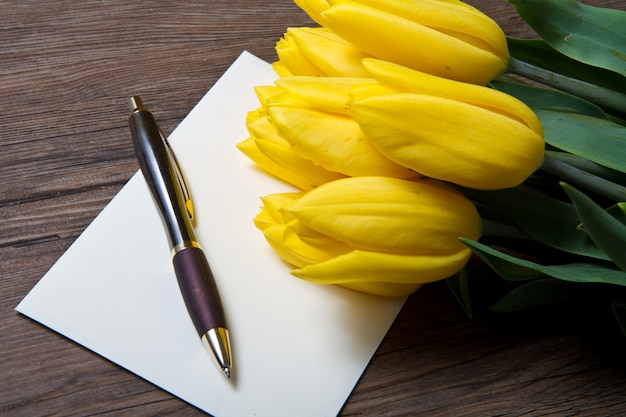 Gelbe tulpen und postkarte