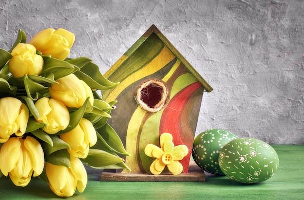Gelbe tulpen, vogelhäuschen und bemalte ostereier mit dekorativer filzblume.