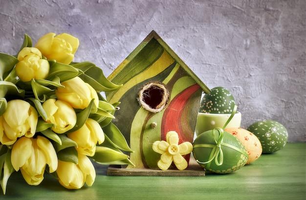 Gelbe tulpen, vogelhäuschen und bemalte ostereier mit dekorativer filzblume