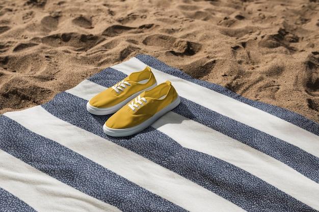 Gelbe turnschuhe auf strandtuch-sommerstimmungsfotografie