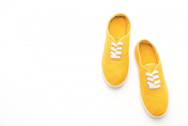 Gelbe turnschuhe auf weißem hintergrund