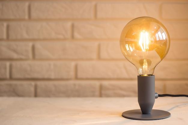 Gelbe unbedeutende moderne lampe im innenraum auf dem hintergrund einer backsteinmauer auf dem desktop