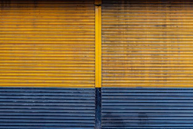 Gelbe und blaue farbe rollender stahlverschlusstürhintergrund.