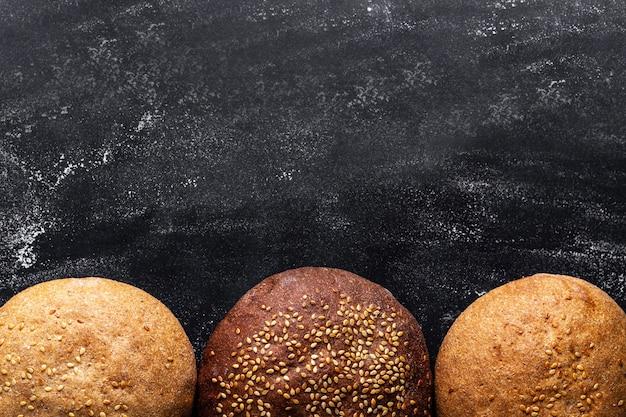 Gelbe und braune sesambrötchen auf einer schwarzen brandung. ansicht von oben. mehl und backwaren. frisches brot. kopieren sie platz