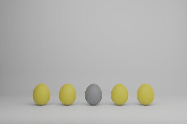Gelbe und graue eier in einer linie auf einem weißen hintergrund