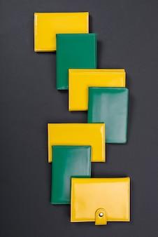 Gelbe und grüne geldbörse auf einer schwarzen matte