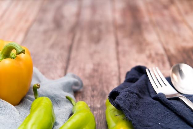 Gelbe und grüne paprika auf den hölzernen hintergründen