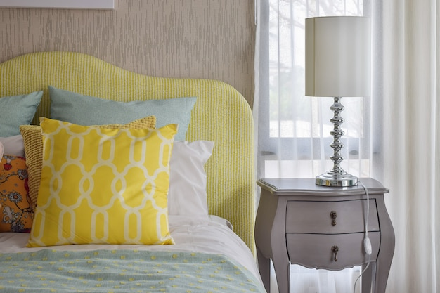 Gelbe und grüne und musterkissen auf klassischem artbett und leselampe auf nachttisch