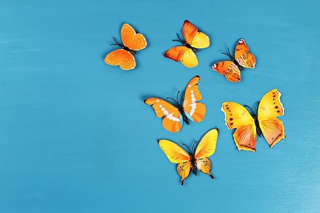 Gelbe und orange schmetterlinge auf blauem hintergrund. ansicht von oben. sommer hintergrund. flach liegen.