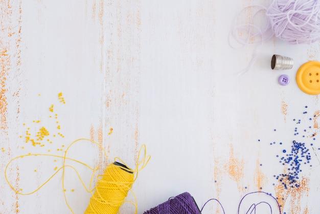 Gelbe und purpurrote garnspule und perlen auf weißem schreibtisch