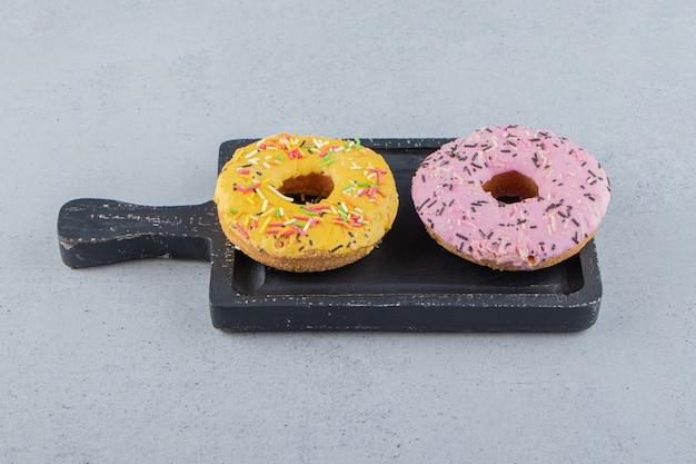 Gelbe und rosa donuts verziert mit streuseln auf schneidebrett. foto in hoher qualität